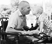 Photo of man in wheelchair with child